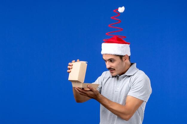 Vorderansicht junger mann, der lebensmittelpaket auf blauem schreibtisch männlicher joblebensmittelservicemensch hält