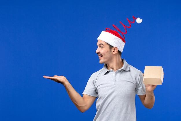 Vorderansicht junger mann, der lebensmittelpaket auf blauem schreibtischlebensmittel-dienstjob des mannes hält