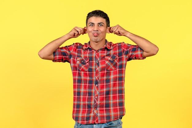 Vorderansicht junger mann, der lustige gesichter auf gelbem hintergrund macht