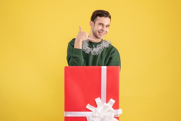 Vorderansicht junger mann, der mich anruft telefonschild, das hinter großer geschenkbox auf gelb steht