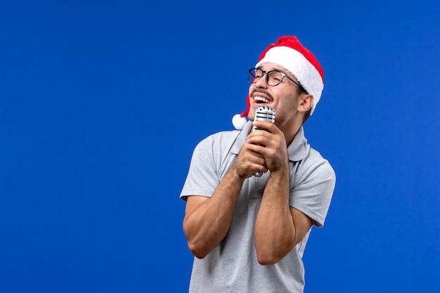 Vorderansicht junger mann, der mikrofon auf blauem schreibtisch neujahrs-sänger-musikmann hält