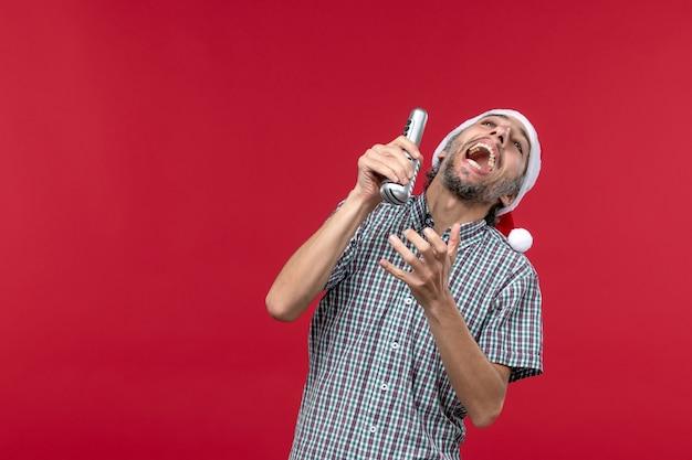 Vorderansicht junger mann, der mikrofon auf dem roten hintergrund hält