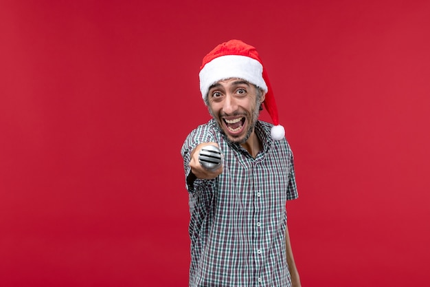 Vorderansicht junger mann, der mikrofon emotional auf rotem hintergrund hält