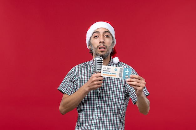 Vorderansicht junger mann, der mikrofon und flugticket auf rotem hintergrund hält
