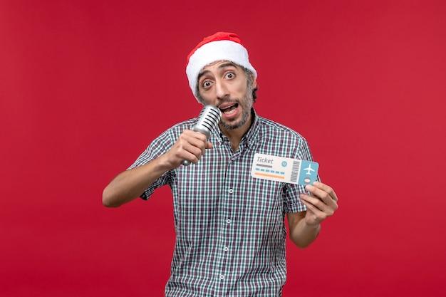 Vorderansicht junger mann, der mikrofon und ticket auf rotem hintergrund hält