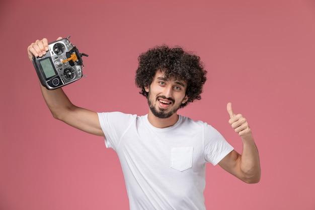 Vorderansicht junger mann, der mit funksteuerung des elektronischen roboters aufwirft