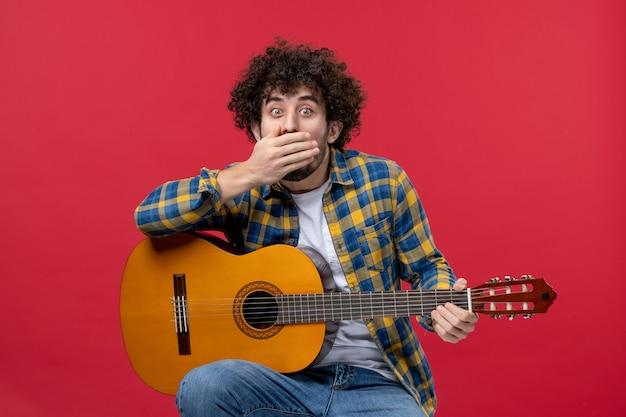 Vorderansicht junger mann, der mit gitarre auf roter wand sitzt live-applaus-musiker spielen farbband-konzertmusik