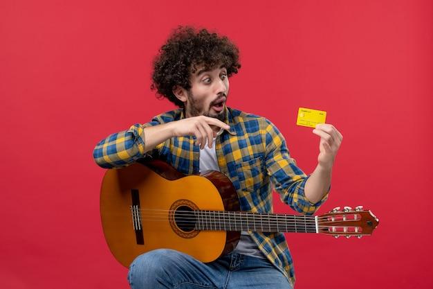 Vorderansicht junger mann, der mit gitarre sitzt und bankkarte auf roter wandmusik-konzertapplaus-farbverkauf live hält