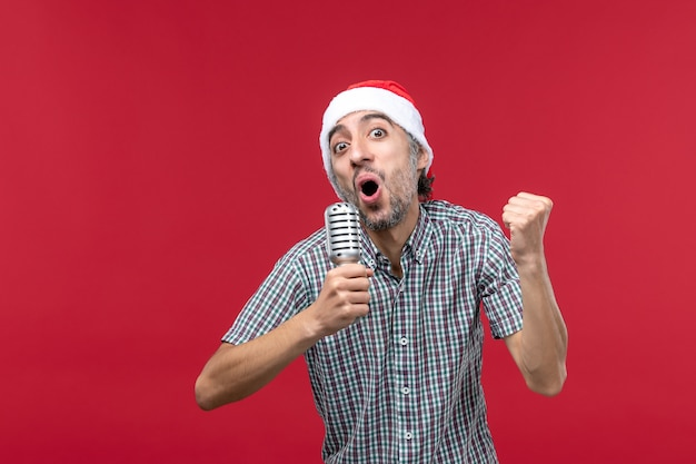 Vorderansicht junger mann, der mit mikrofon auf rotem schreibtisch singt