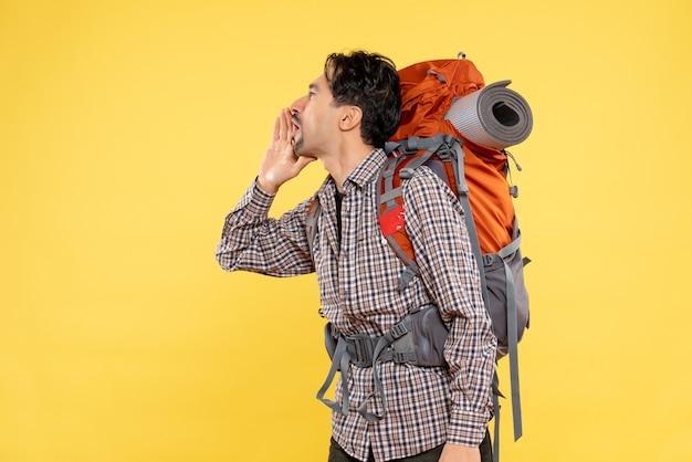Vorderansicht junger mann, der mit rucksack wandern geht und jemanden auf gelbem hintergrund anruft