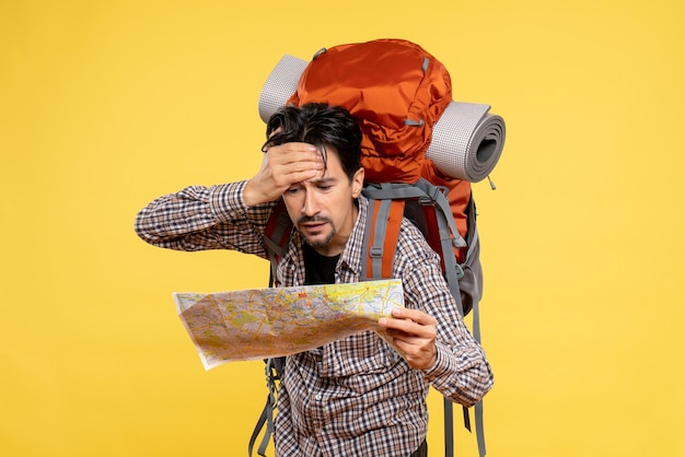 Vorderansicht junger mann, der mit rucksack wandern geht und karte auf gelbem hintergrund beobachtet