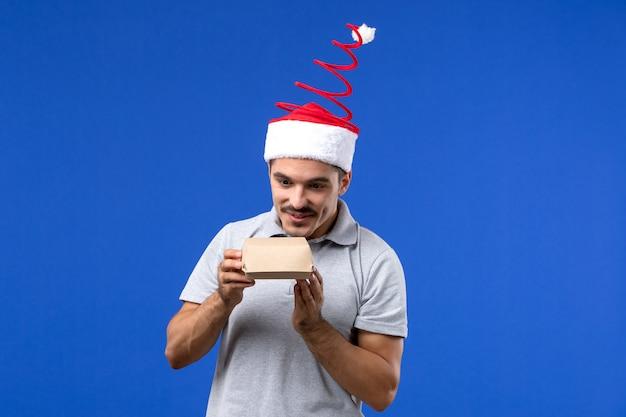 Vorderansicht junger mann, der nahrungsmittelpaket auf männlichem joblebensmittelservicemensch der blauen wand hält