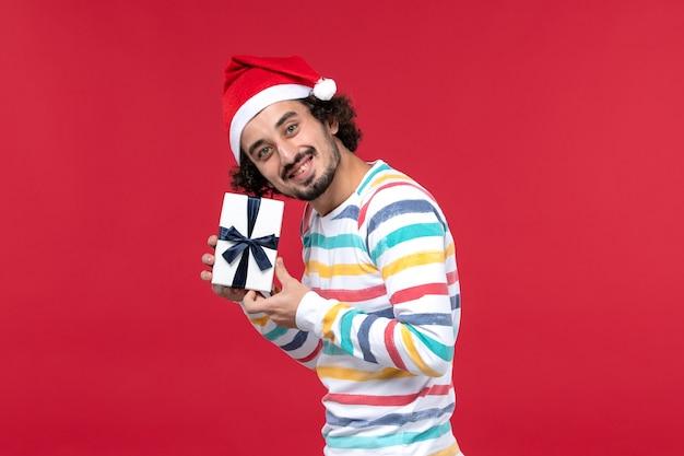 Vorderansicht junger mann, der neujahrsgeschenk auf dem roten hintergrundfeiertags-neujahrsgefühl hält