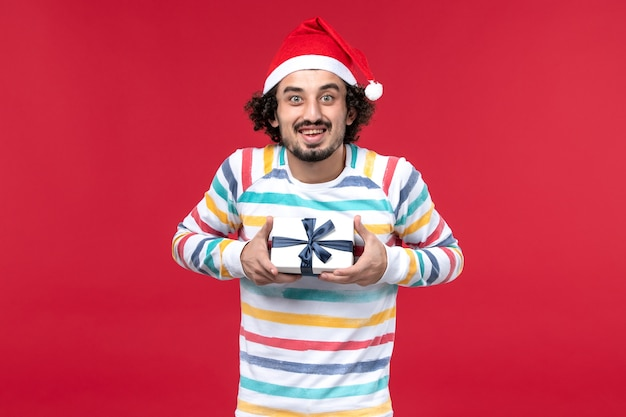 Vorderansicht junger mann, der neujahrsgeschenk auf roten hintergrundfeiertagen rotes neues jahr hält