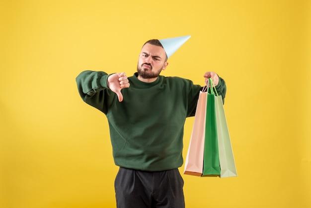 Vorderansicht junger mann, der pakete mit geschenken auf gelbem hintergrund hält