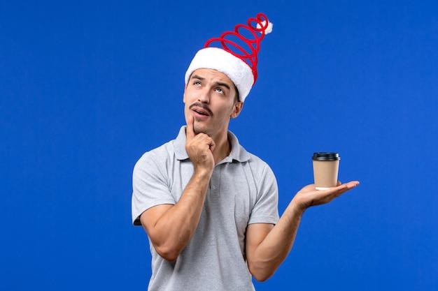 Vorderansicht junger mann, der plastikkaffeetasse auf blauem wandgefühl neujahrsmann hält
