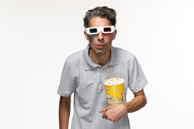 Vorderansicht junger mann, der popcorn in d sonnenbrille auf weißer oberfläche isst