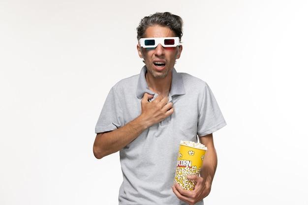Vorderansicht junger mann, der popcorn in d sonnenbrillen isst film auf weißer oberfläche essen