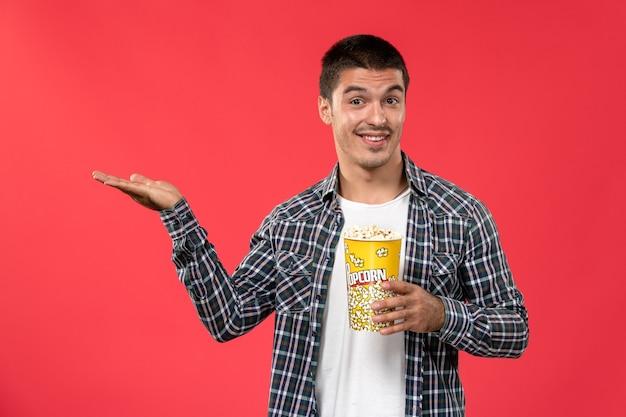 Vorderansicht junger mann, der popcorn-paket auf der hellroten wand männliches kino kino film spaß zeiten hält