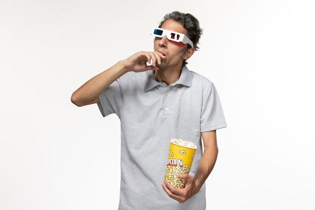 Vorderansicht junger mann, der popcorn-paket hält und d sonnenbrille auf weißer oberfläche trägt
