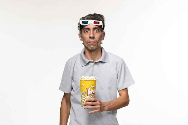 Vorderansicht junger mann, der popcorn-paket in d sonnenbrille auf der weißen oberfläche hält