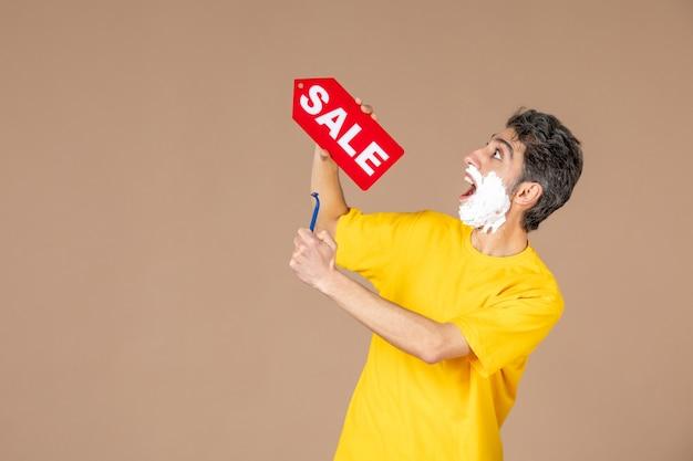Vorderansicht junger mann, der rasiermesser und rotes verkaufs-namensschild auf rosa hintergrund hält