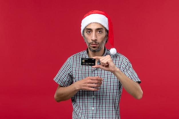 Vorderansicht junger mann, der schwarze bankkarte auf dem roten hintergrund hält