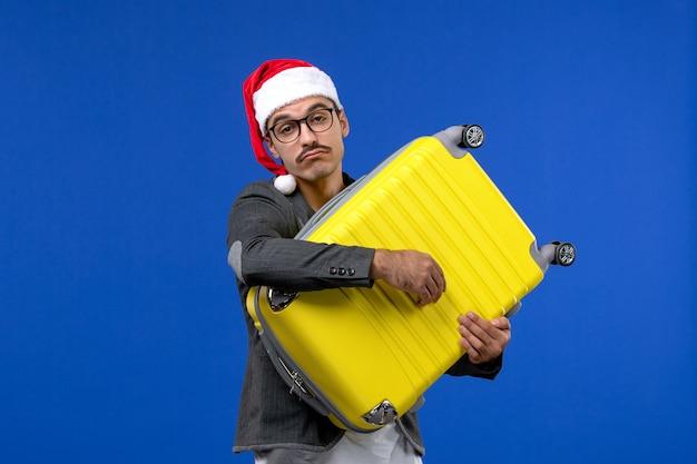 Vorderansicht junger mann, der schwere gelbe tasche auf flugzeugurlaub der blauen wandflüge trägt