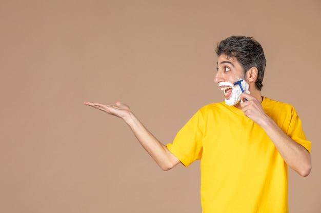 Vorderansicht junger mann, der sein geschäumtes gesicht auf rosa hintergrund rasiert