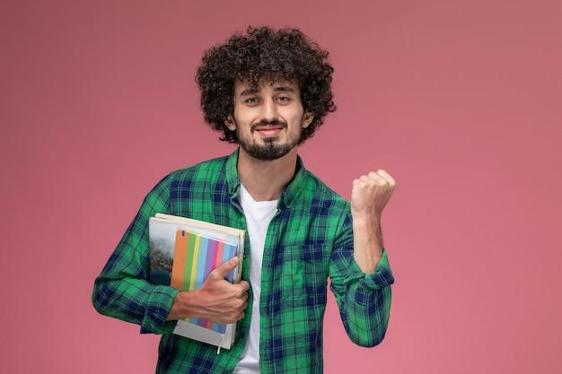 Vorderansicht junger mann, der seine hand mit notizbüchern drückt