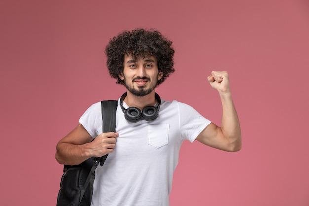 Vorderansicht junger mann, der seine stärke zeigt und kopfhörer benutzt