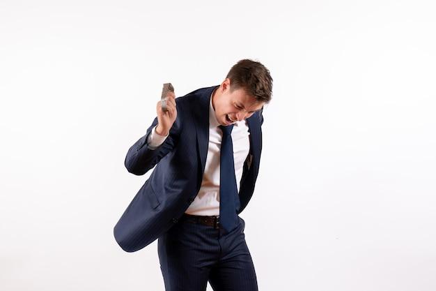Vorderansicht junger mann, der seine uhren im klassischen anzug auf weißem hintergrund wirft