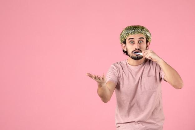 Vorderansicht junger mann, der seine zähne auf rosa hintergrund reinigt