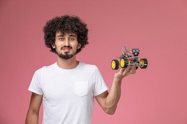 Vorderansicht junger mann, der seinen elektronischen roboter hält