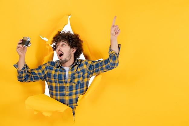 Vorderansicht junger mann, der selfie-foto mit kamera auf gelbem hintergrund macht