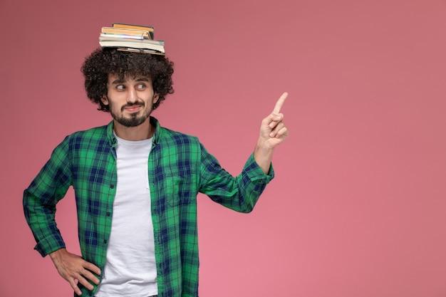 Vorderansicht junger mann, der seltsame pose auf rosa hintergrund gibt