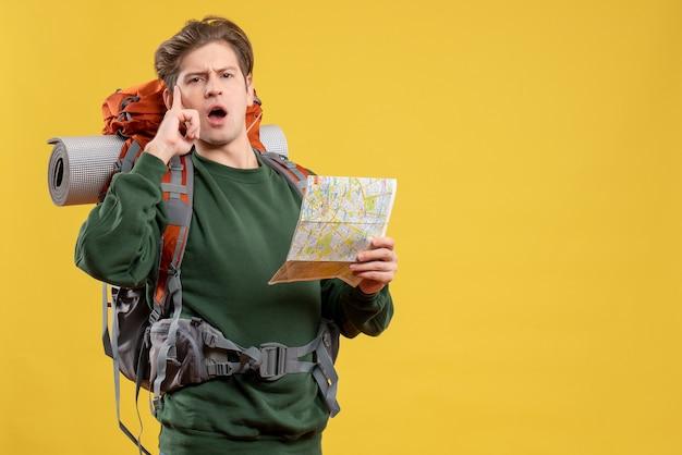Vorderansicht junger mann, der sich auf das wandern vorbereitet, karte beobachtend