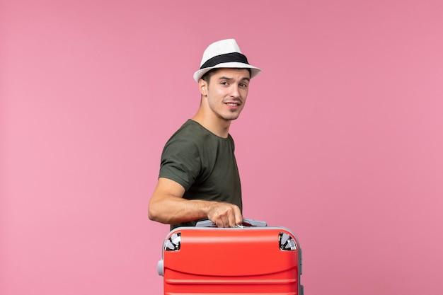 Vorderansicht junger mann, der sich auf den urlaub auf dem rosafarbenen raum vorbereitet