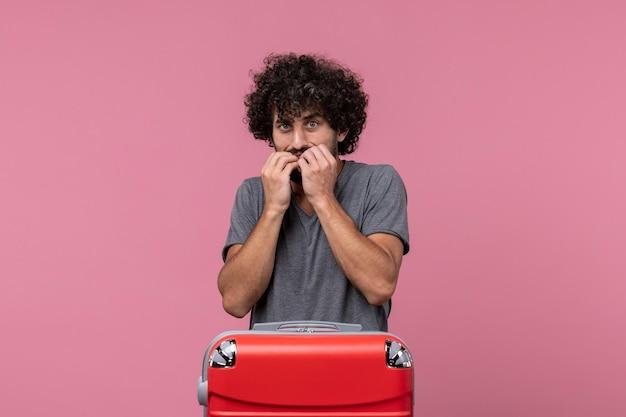 Vorderansicht junger mann, der sich auf den urlaub fertig macht, aber angst auf rosa raum hat