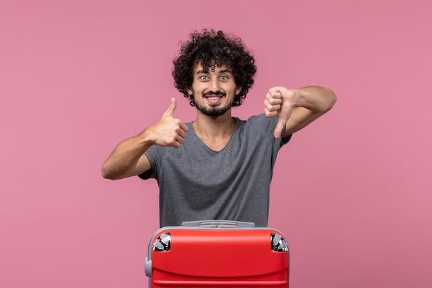 Vorderansicht junger mann, der sich auf den urlaub fertig macht und auf rosafarbenem raum lächelt