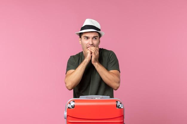 Vorderansicht junger mann, der sich auf den urlaub mit hut auf rosafarbenem raum vorbereitet