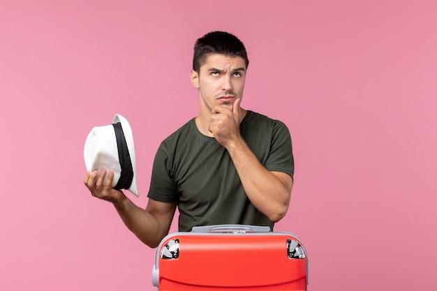 Vorderansicht junger mann, der sich auf den urlaub vorbereitet, mit großer tasche, die auf rosa raum denkt