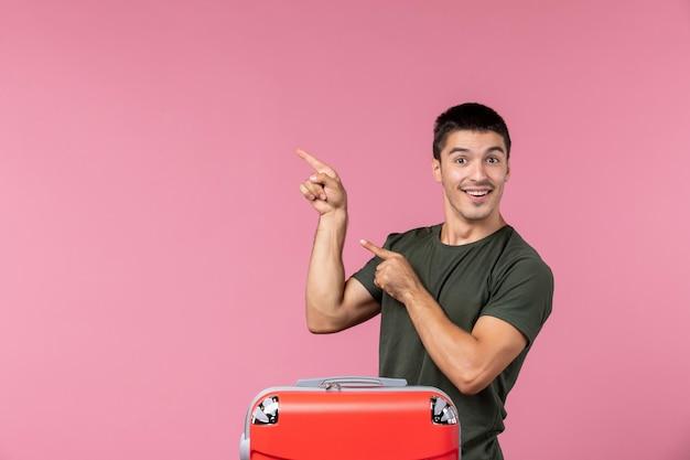 Vorderansicht junger mann, der sich auf den urlaub vorbereitet, mit großer tasche, die auf rosafarbenem raum lächelt
