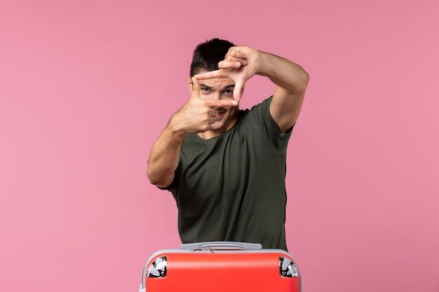 Vorderansicht junger mann, der sich auf den urlaub vorbereitet und auf rosafarbenem raum posiert