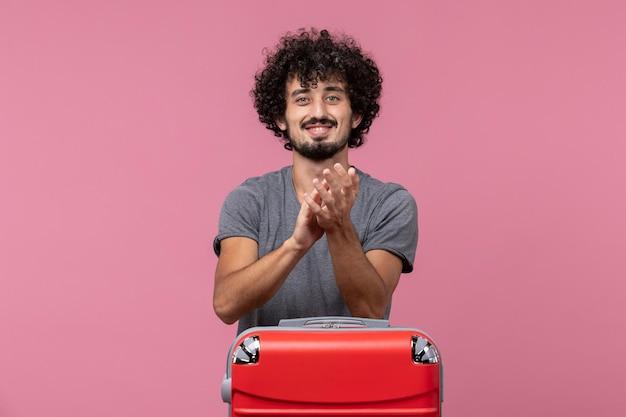 Vorderansicht junger mann, der sich auf den urlaub vorbereitet und auf rosafarbenen raum klatscht