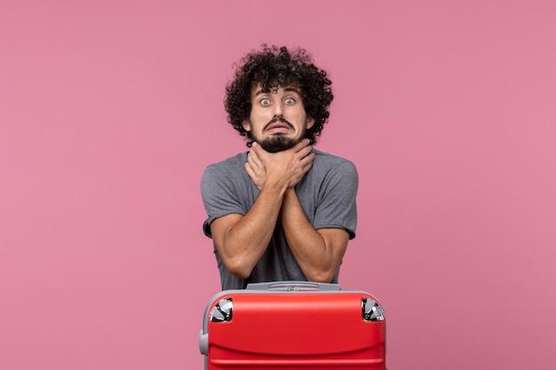Vorderansicht junger mann, der sich auf den urlaub vorbereitet und sich auf rosafarbenem raum erstickt