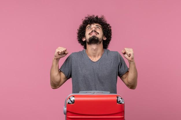 Vorderansicht junger mann, der sich auf den urlaub vorbereitet und sich über den rosa raum freut