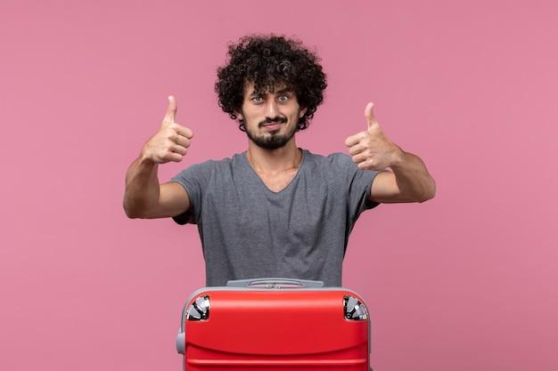 Vorderansicht junger mann, der sich auf die reise auf dem rosafarbenen raum vorbereitet