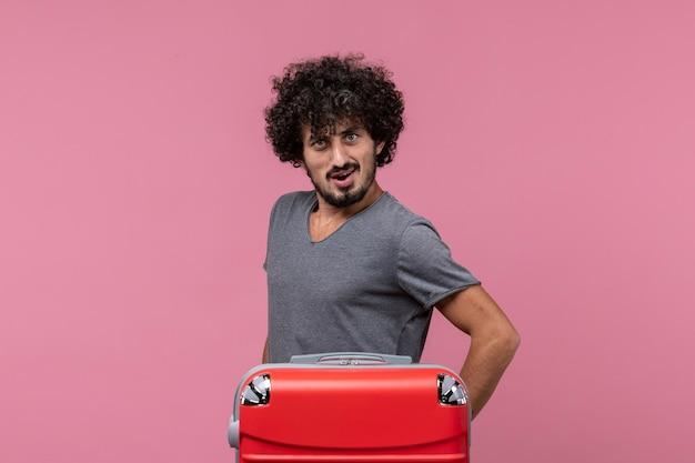 Vorderansicht junger mann, der sich auf die reise vorbereitet und seine stärke auf rosafarbenem raum zeigt