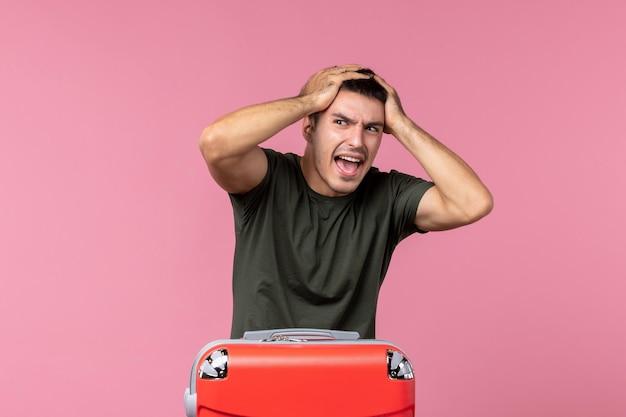 Vorderansicht junger mann, der sich auf die reise vorbereitet und seinen kopf auf rosa raum hält